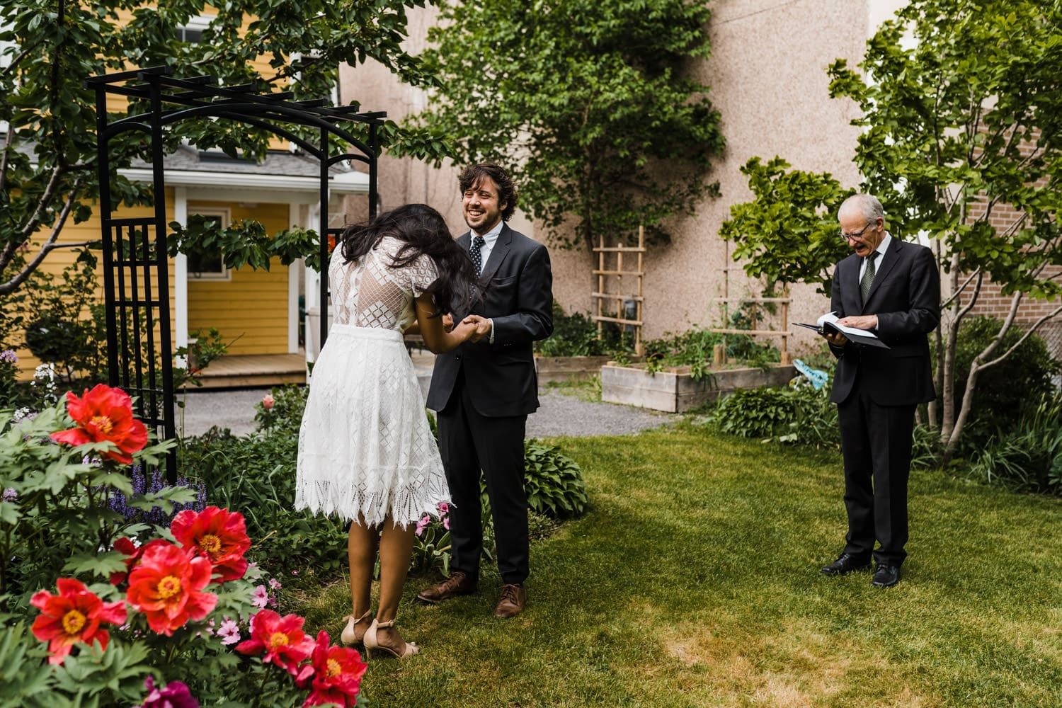 bride and groom laugh together during wedding ceremony - small backyard ceremony