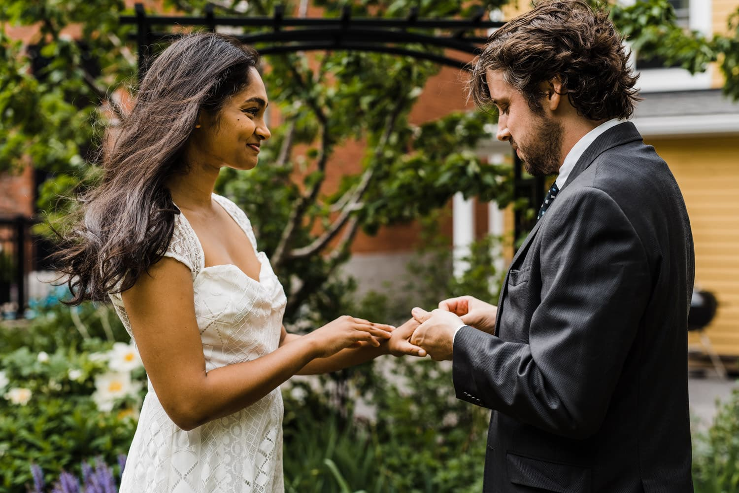 couple exchanges rings during small backyard ceremony