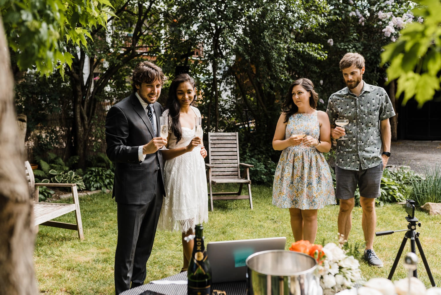 couple shares a toast with their families on livestream - small backyard wedding ottawa