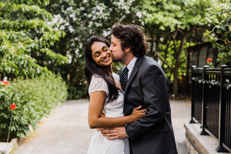 groom kisses bride's cheek - small backyard ceremony ottawa