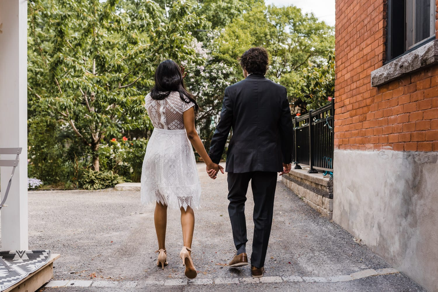 couple holds hands and walks through the backyard together